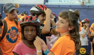 Making sure the helmets fits correctly at the Freewheels Bike Camp.